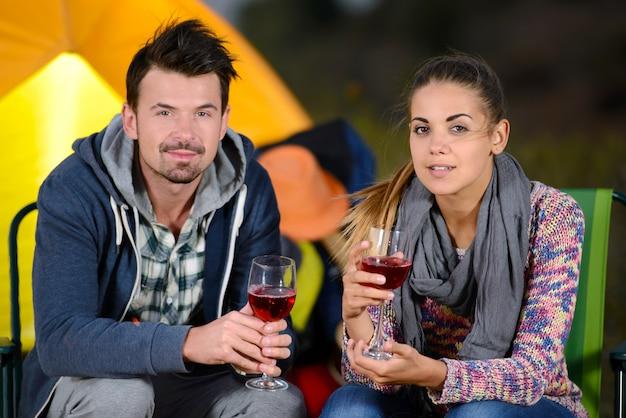 Charmant couple près d'un feu en camping buvant du vin.