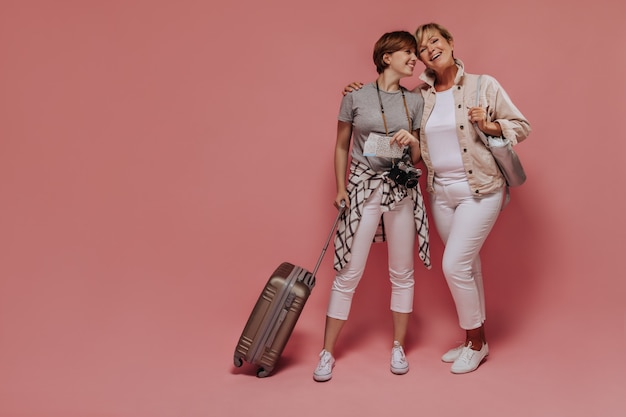 Charmant deux dames avec une coiffure courte et fraîche dans des vêtements modernes légers posant avec des billets, un appareil photo et une valise et souriant sur fond rose.