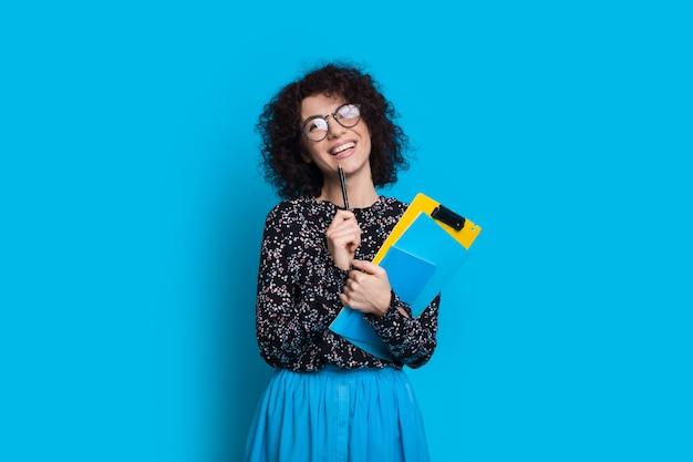 Charmant étudiant aux cheveux bouclés tenant des livres tout en posant dans une robe sur un mur bleu avec un espace vide