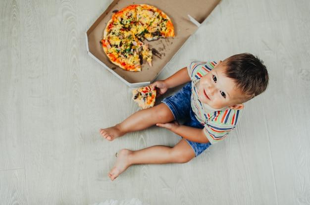 Charmant garçon assis sur le sol, manger une pizza vue de dessus