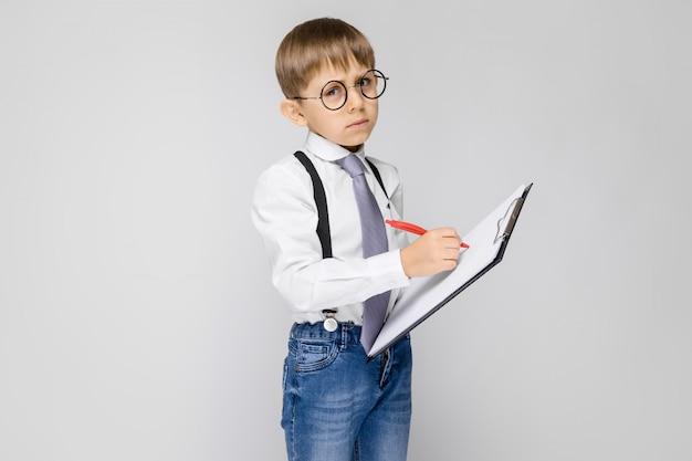 Un charmant garçon en chemise blanche, bretelles, cravate et jean léger se dresse sur un gris