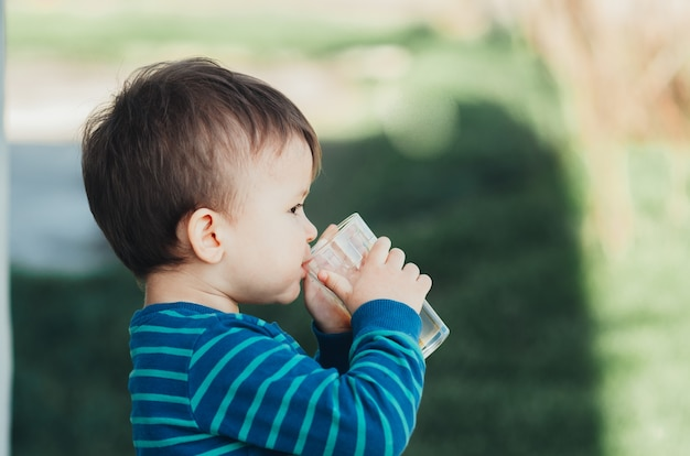 Charmant garçon dans la nature, boire du jus de pomme