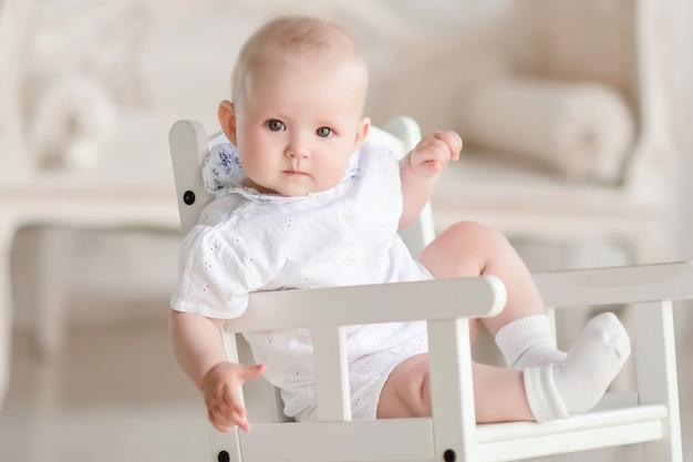 Charmant garçon nouveau-né est assis sur la chaise dans le studio