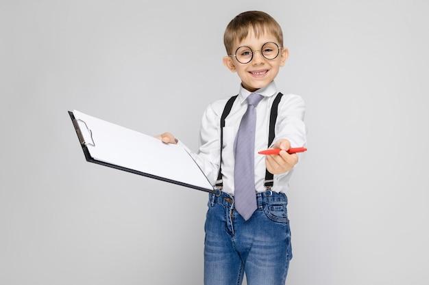 Un charmant garçon vêtu d'une chemise blanche, de bretelles, d'une cravate et d'un jean léger