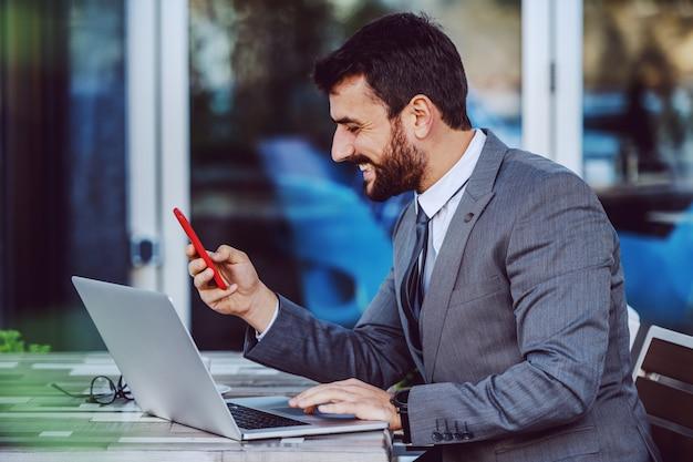 Charmant homme d'affaires barbu caucasien souriant en costume à l'aide d'un téléphone intelligent alors qu'il était assis dans le café. sur la table se trouve un ordinateur portable et du café.