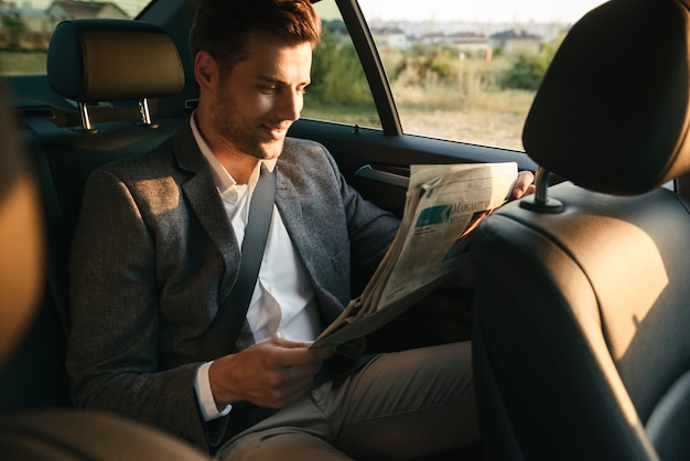 Charmant homme d'affaires lisant le journal