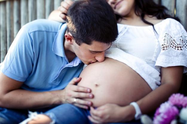 Charmant homme embrasse le ventre de femme enceinte tendre de sa dame en chemise blanche