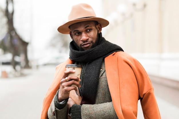 Charmant homme posant à l'extérieur tout en tenant une tasse de café