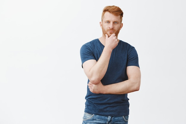 Charmant homme rousse masculin en t-shirt bleu, touchant la barbe et regardant avec un regard réfléchi, pensant, prenant une décision ou un choix sur un mur gris, ayant une idée intéressante à l'esprit