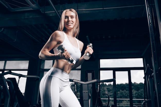 Charmant jeune athlète s'entraîne avec des haltères dans la salle de gym. concept de musculation