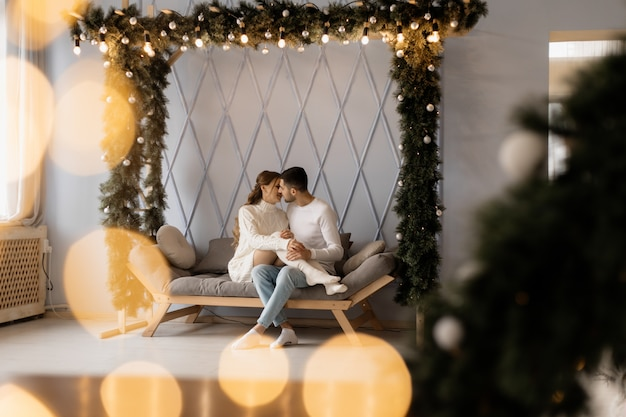 Charmant jeune couple en vêtements de maison blancs confortables pose dans une chambre avec arbre de noël