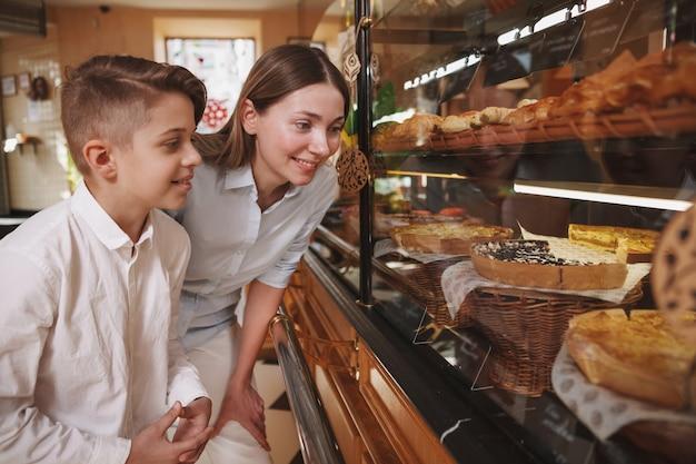 Charmant jeune garçon shopping pour les desserts avec sa maman à la boulangerie, copiez l'espace