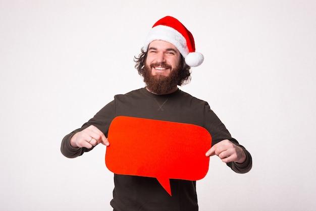 Charmant jeune homme avec barbe souriant et tenant la bulle de dialogue rouge