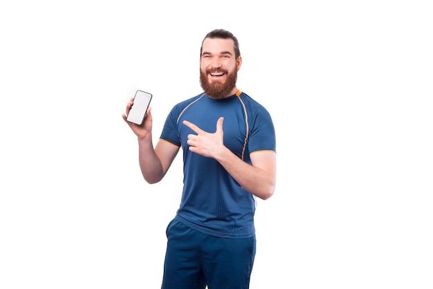 Charmant jeune homme barbu fitness pointant sur smartphone sur blanc
