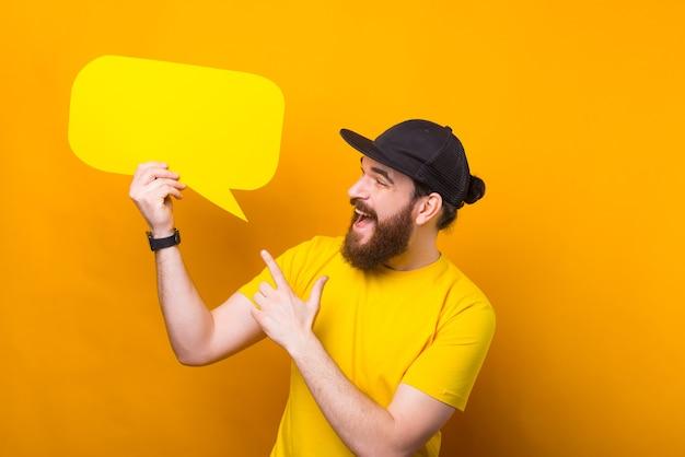 Charmant jeune homme barbu pointant sur la bulle de dialogue jaune