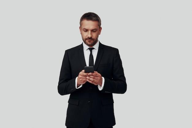 Charmant jeune homme en costume complet à l'aide d'un téléphone intelligent en se tenant debout sur fond gris