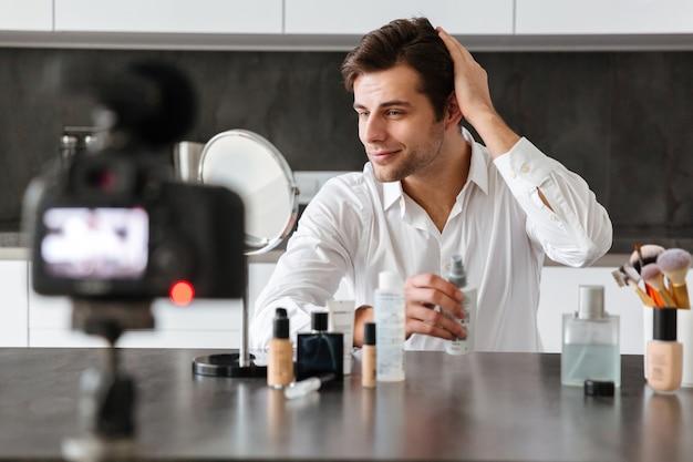 Charmant jeune homme filmant son épisode de blog vidéo