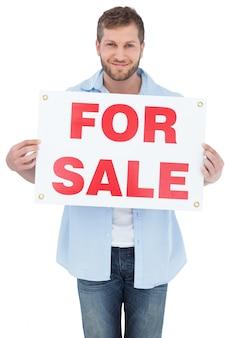 Charmant jeune homme tenant une pancarte à vendre