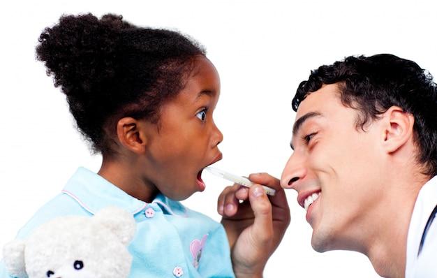 Charmant médecin prenant la température des petites filles