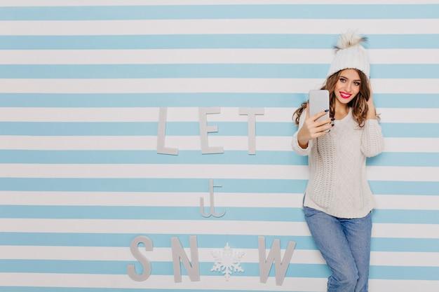 Charmant modèle de 23 ans avec un sourire charmant fait une photo au téléphone. portrait en pied sur mur rayé