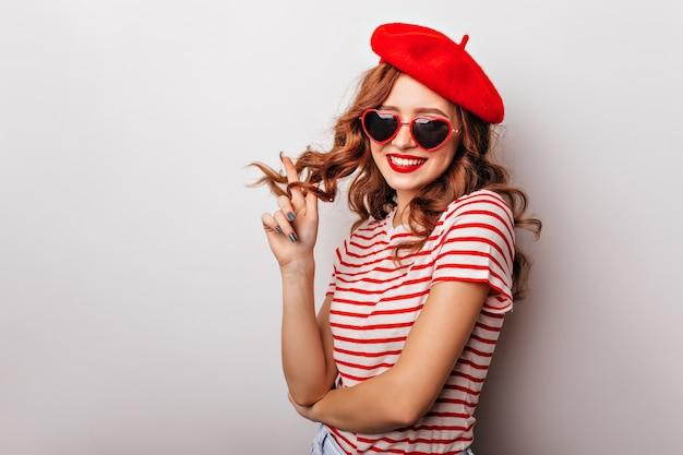 Charmant modèle féminin jouant avec des cheveux bouclés au gingembre. élégante femme française en béret debout sur un mur blanc.