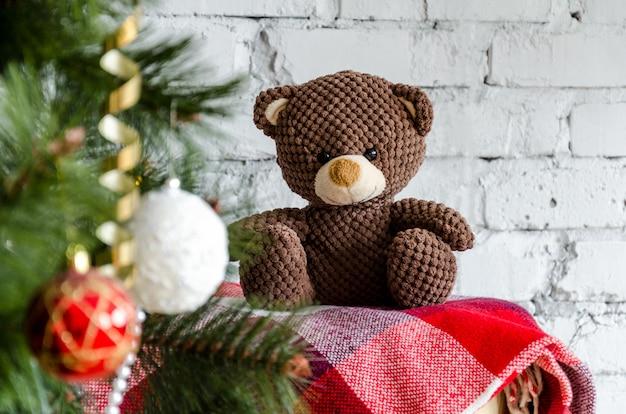 Charmant ours en peluche brun assis sur une couverture rouge près de l'arbre de noël