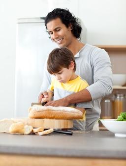 Charmant père coupe du pain avec son fils
