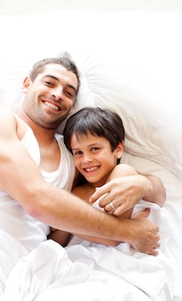 Charmant père et son fils regardant la caméra sur le lit