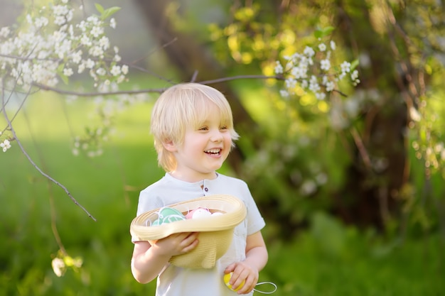 Charmant petit garçon à la recherche d'oeufs de pâques dans le parc du printemps le jour de pâques