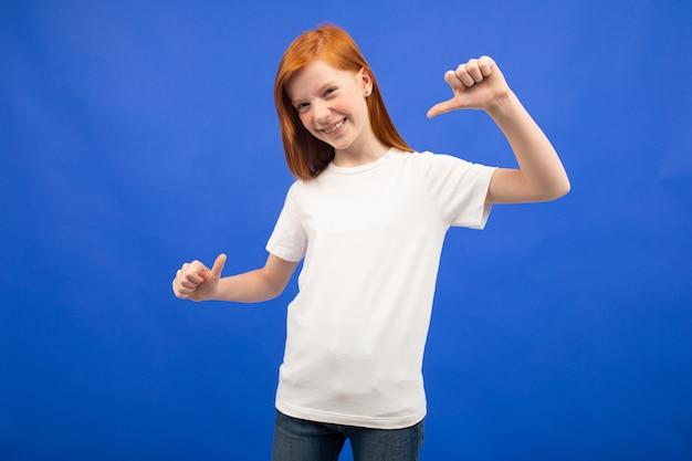 Charmante adolescente aux cheveux roux dans un t-shirt blanc avec une maquette imprimée bleu