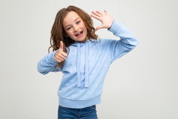 Charmante adolescente dans un sweat à capuche bleu montre six doigts sur un fond gris clair