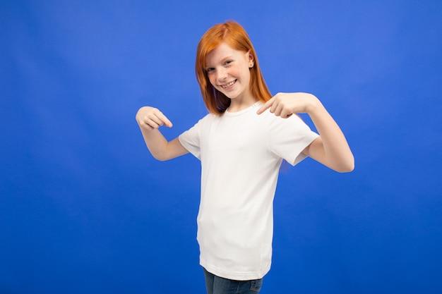 Charmante adolescente rousse dans un t-shirt blanc montre un espace d'impression vierge sur bleu