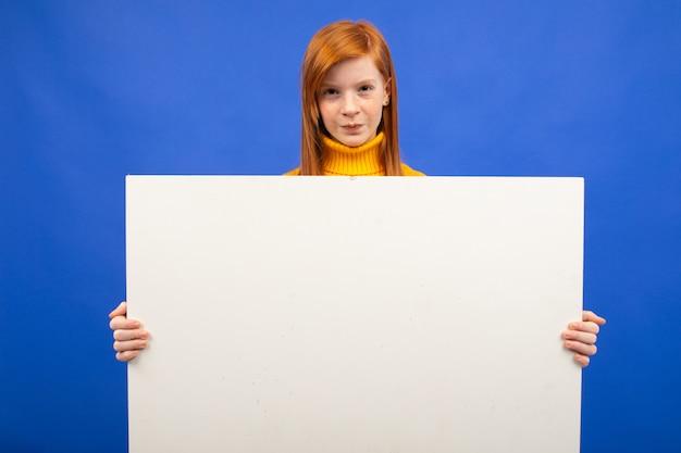 Charmante adolescente rousse européenne tenant une affiche en papier vierge pour la publicité sur bleu