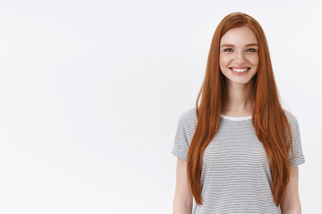 Charmante et agréable étudiante rousse sympathique souriante joyeusement la caméra regarde sous tension participer à un cours de danse apprenant un nouveau passe-temps debout mur blanc diverti, concept de style de vie