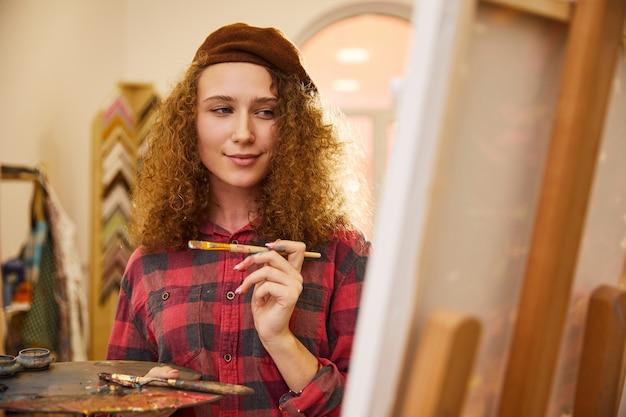 Une charmante artiste rousse dessine une image