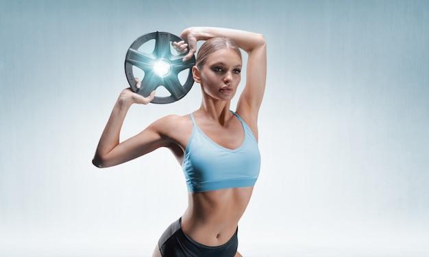 Charmante athlète posant dans le studio avec des poids dans ses mains. le concept de sport, musculation, nutrition sportive.