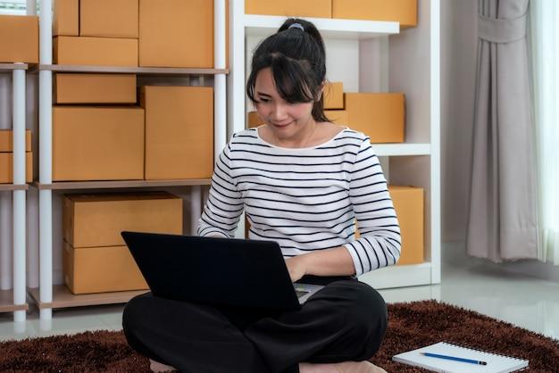 Charmante belle adolescente asiatique propriétaire femme d'affaires travaille assis sur le sol pour les achats en ligne, à la recherche de l'ordre dans un ordinateur portable avec du matériel de bureau, concept de style de vie d'entrepreneur