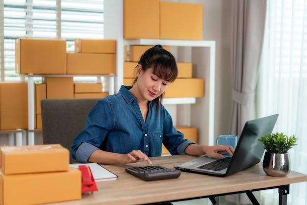 Charmante belle adolescente asiatique propriétaire femme d'affaires travaille à la maison pour les achats en ligne, calculer le prix des marchandises avec un ordinateur portable avec du matériel de bureau, concept de style de vie d'entrepreneur