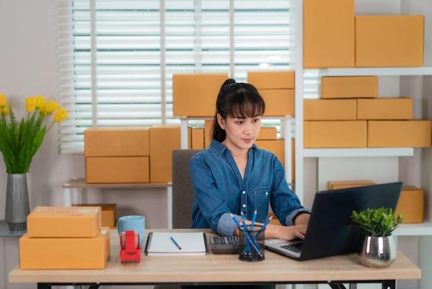 Charmante belle adolescente asiatique propriétaire femme d'affaires travaille à la maison pour les achats en ligne, à la recherche de la commande dans un ordinateur portable avec du matériel de bureau, concept de style de vie d'entrepreneur