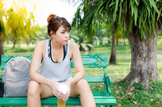 Charmante belle femme asiatique assis sur un banc dans le parc thew.