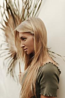Charmante belle femme blonde bronzée aux cheveux longs vêtue d'un haut court kaki semble droite et détient une feuille de palmier sèche près du mur blanc