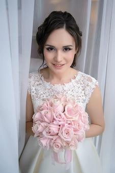 Charmante belle mariée à la fenêtre avec un bouquet de mariage de roses roses le matin