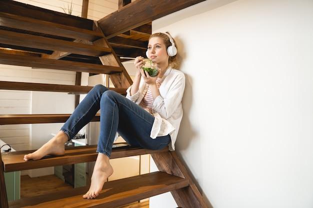 Charmante blonde assise dans les escaliers en mangeant des algues