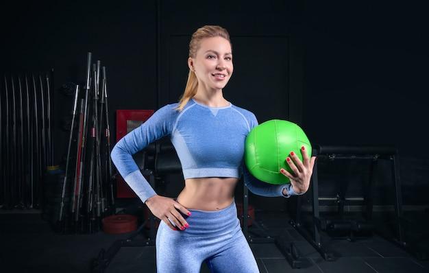 Charmante blonde posant dans la salle de gym avec un ballon de fitness. vue de face. le concept de sport, musculation, fitness. technique mixte
