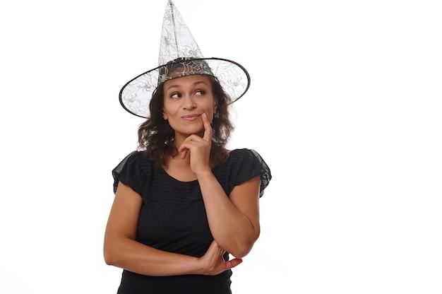 Charmante brune hispanique en chapeau de carnaval de sorcière et tenue noire, tient le doigt sur son menton et sourit avec un joli sourire à pleines dents, regardant mystérieusement l'arrière-plan blanc de l'espace de copie. notion d'halloween