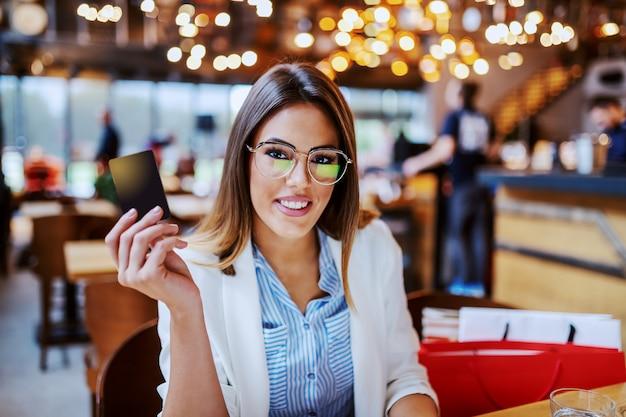 Charmante brune à la mode caucasienne avec un beau sourire tenant une nouvelle carte de crédit qu'elle vient d'obtenir.