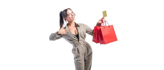 Charmante brune posant dans le studio avec des paquets rouges et une carte bancaire