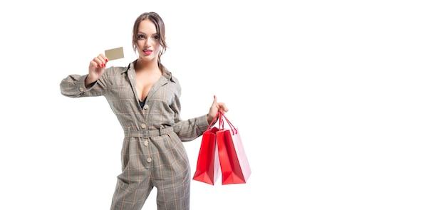 Charmante brune posant avec des paquets rouges et une carte bancaire