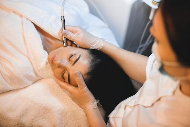 Une charmante brune a une procédure de spa du visage en position couchée les yeux fermés