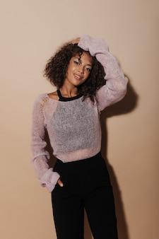 Charmante dame aux cheveux bruns moelleux et maquillage cool en pull léger, haut foncé et pantalon noir sur un mur isolé.